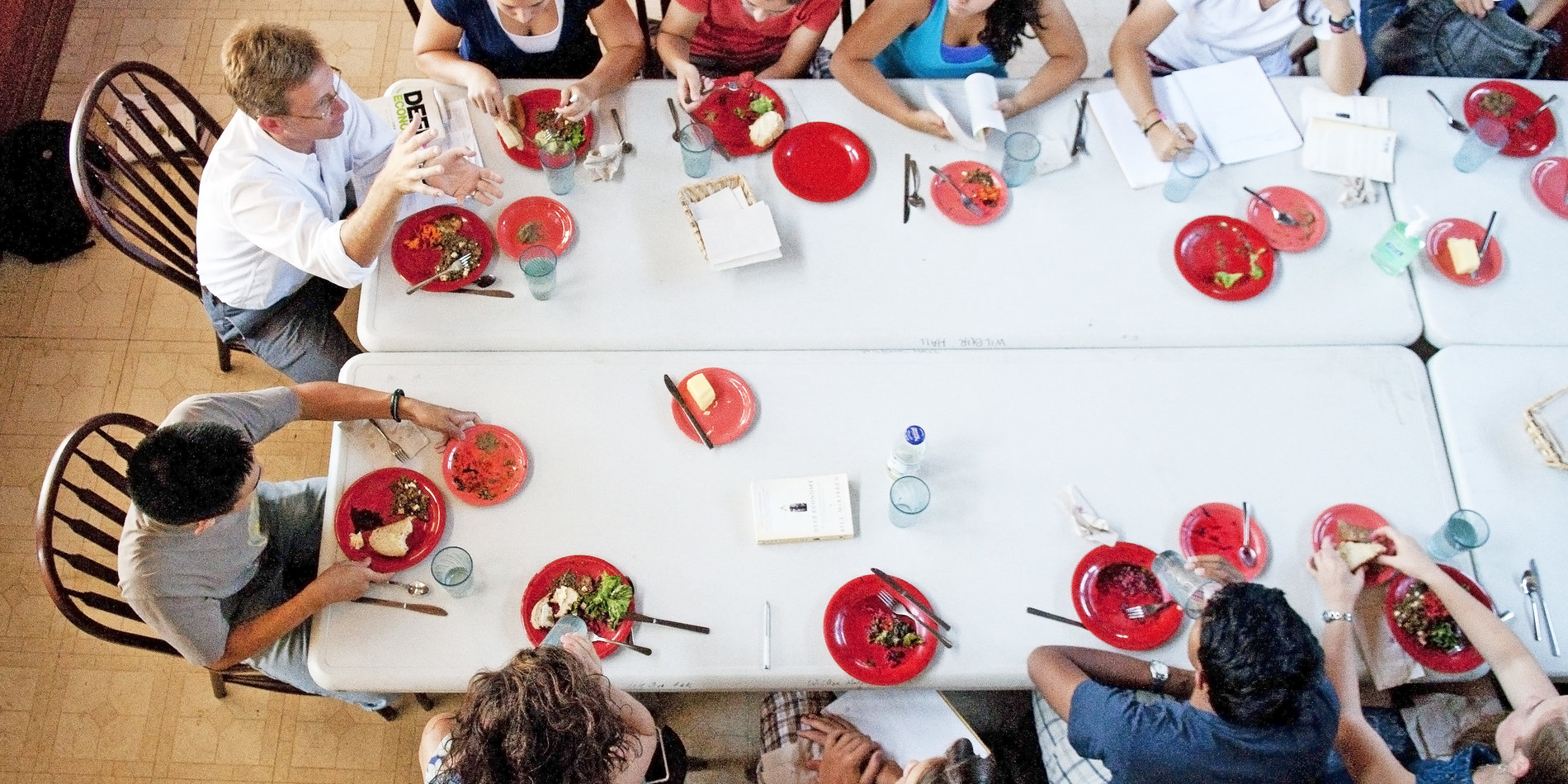 Associate professor of political science Rob Reich (seated at the end of the table in white shirt and glasses) and his students eat food they prepared for his Food and Politics course, part of Sophomore College. Credit Linda A. Cicero / Stanford News Service