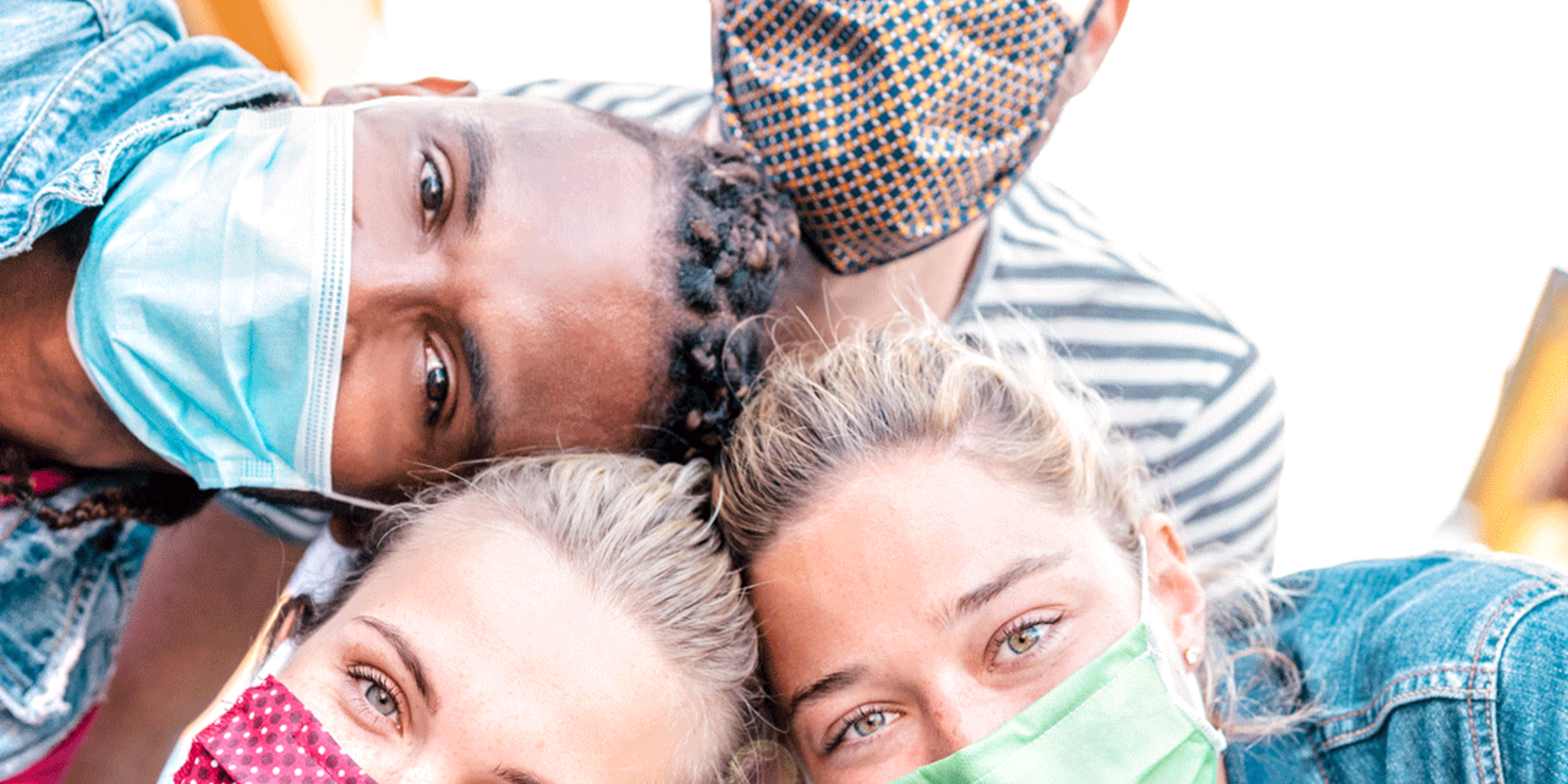 Tile image featuring a diverse group of individuals posing together in their face coverings while outdoors.